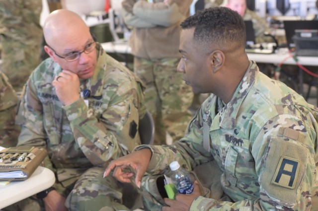 "Capt. Zantionyo Goodwin (right), a maintenance observer coach/trainer with First Army's 174th Infantry Brigade, talks with Lt. Col. Ron Humphrey, chief of Logistics for the Pennsylvania Army National Guard's 28th Infantry Division, during the 28th ID's culminating training exercise at Fort Hood, Texas, Jan. 30, 2018. The 28th ID is preparing to deploy to the Middle East, where the unit will support Operation Spartan Shield. ""First Army has been very helpful, both in training and in the real world, assisting us with things like (requests for information). Overall, I think they've done well with coaching and mentoring us through the exercise process,"" Humphrey said. ""I'm very proud of my team. We are looking to integrate and learn the mission set, and we're very anxious to get over there."" (Photo altered for security purposes.)"
