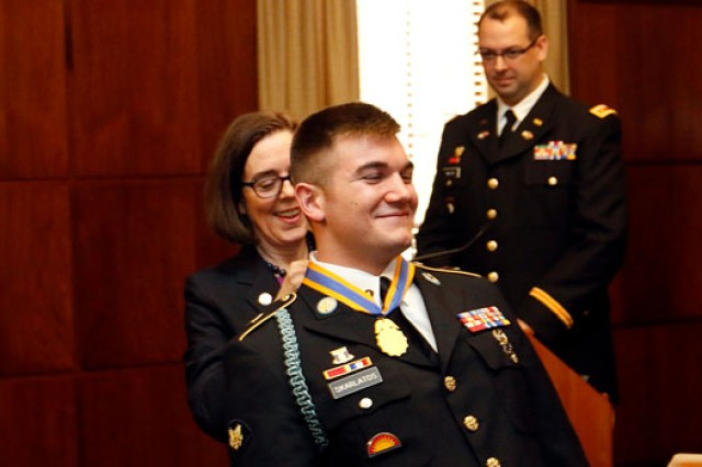 Oregon Gov. Kate Brown places the Oregon Distinguished Service Medal on the neck of Oregon Army National Guard Spc. Aleksander Skarlatos during a ceremony at the state capitol building in Salem, Oregon, Feb. 17, 2016.