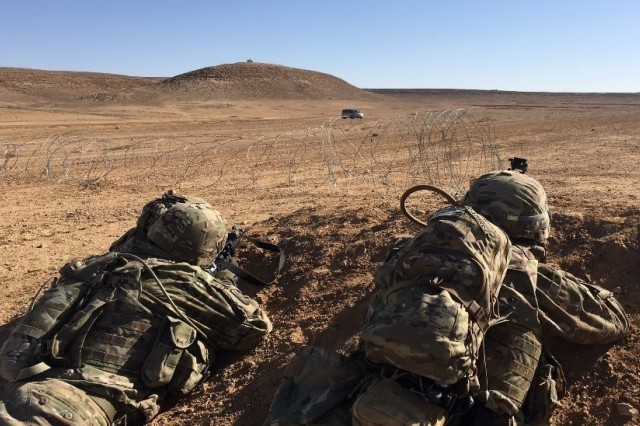 "Soldiers from Bravo Company ""Bushmasters,"" 1st Battalion, 184th Infantry Regiment, California Army National Guard, locate cover and return fire after receiving simulated small-arms fire during a training exercise near Amman, Jordan on February 2, 2018. The scenario based training allowed Bushmaster leadership to assess their company's ability to set up a roadblock, create an entry control point, and deny enemy access to key terrain."