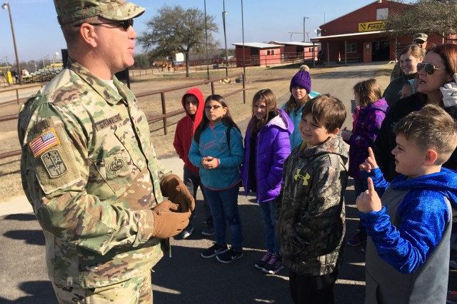 Sgt. 1st Class Robert D. Grawburg, NCOIC of the U.S. Army Operational Test Command's Maneuver Test Directorate, greets Florence, Texas Elementary School students, as they arrive to the 1st Cavalry Division Horse Cavalry Detachment Thursday under Fort Hood's Adopt-A-School program, as a reward for their participation in the Academic University Interscholastic League.