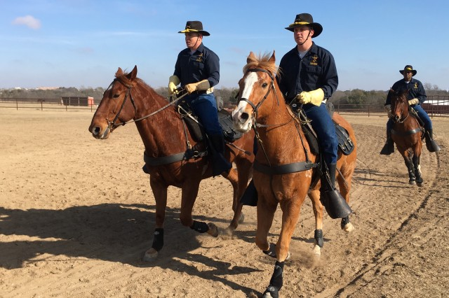1st Cavalry Division Horse Cavalry Detachment Troopers (from left to right) Sgt. Michael Mascunana, riding Rome; Sgt. Chance Barlow, riding Jedi; and�1st Sgt. Romerick Whiteing, riding Dragoon, perform during a demonstration of mounted battle drills of the 1880s, during�a Fort Hood�Adopt-A-School program visit by Florence, Texas Elementary School students to the Horse Platoon stables Thursday.