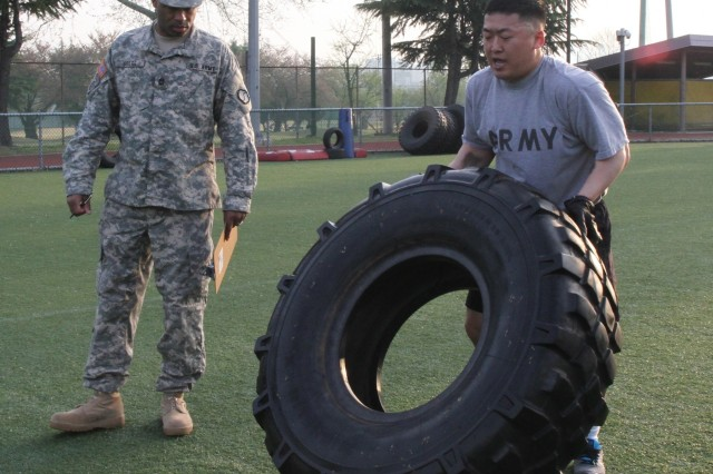 Sgt. Kim, Yong-i, a 403rd Army Field Sustainment Brigade service member, flips the tire during the functional fitness test course portion of the Best Warrior Competition 2015 at Camp Walker's Kelly Field April 16.