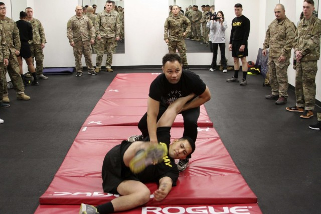 FORT HOOD, Texas- Retired professional mixed martial arts fighter, Josh Koscheck, demonstrates a takedown move to Soldiers of 3rd Armored Brigade Combat Team, 1st Cavalry Division here Feb. 6. Koscheck, taught Soldiers some basic grappling, takedown and submission moves while also teaching life lessons.