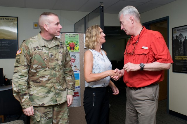 FORT SHAFTER - Ret. Col. Walter M. Herd (right), Army Transition Division director at the Human Resources Command Center of Excellence, presents a challenge coin to Sabrina Newman (center) Transition Services Specialist, Military Personnel Division, U.S. Army Garrison-Hawaii, at Fort Shafter, Feb. 2. Sgt. Maj. Jason Schmidt (left), command sergeant major, Installation Management Command-Pacific, attended a meeting with Herd at the Transition Assistance Program Center. (U.S. Army photo by Kristen Wong, Oahu Publications)