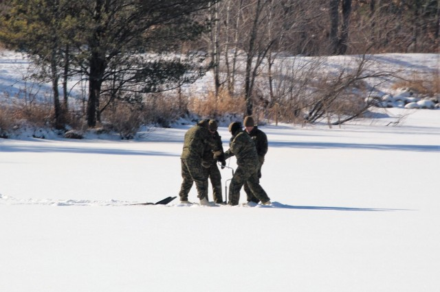 Marines at Fort McCoy for the 2nd Marine Air Wing's Ullr Shield exercise work on drilling a hole in the ice while managing water filtration operations at Big Sandy Lake on South Post on Jan. 17, 2018, at Fort McCoy, Wis. Ullr Shield is a training exercise designed to improve 2nd Marine Aircraft Wing's capabilities in extreme cold-weather environments. The 2nd Marine Aircraft Wing is headquartered at Marine Corps Air Station Cherry Point, N.C. Hundreds of Marines participated in the exercise at Fort McCoy. (U.S. Army Photo by Scott T. Sturkol, Public Affairs Office, Fort McCoy, Wis.)