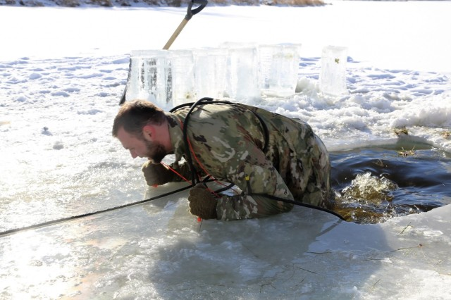 A Soldier participates in cold-water immersion training at an ice-covered Big Sandy Lake as part of training for the Cold-Weather Operations Course 18-02 on Jan. 17, 2018, at Fort McCoy, Wis. The Soldier was one of 25 students in the course. In addition to cold-water immersion training, students were trained on a variety of cold-weather subjects, including skiing and snowshoe training as well as how to use ahkio sleds and other gear. Training also focused on terrain and weather analysis, risk management, cold-weather clothing, developing winter fighting positions in the field, camouflage and concealment, and numerous other areas that are important to know in order to survive and operate in a cold-weather environment. The training is coordinated through the Directorate of Plans, Training, Mobilization and Security at Fort McCoy. (U.S. Army Photo by Scott T. Sturkol, Public Affairs Office, Fort McCoy, Wis.)