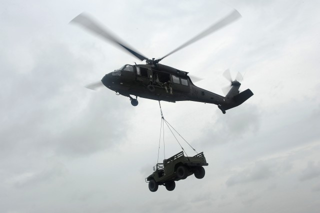 A UH-60 Black Hawk helicopter carries a Humvee during a training mission at Scott Air Force Base, Ill., on Sept. 6, 2014.