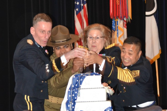 The command team of America's First Corps along with representatives of the youngest and oldest service members assigned to the corps, cut the cake with a ceremonial saber as part of a military tradition celebrating the corps centennial. From left to right: Lt. Gen. Gary J. Volesky, commanding general of America's First Corps and Joint Base Lewis McChord; Spc. Javon Woodruff, honor guard member, 2nd Assault Helicopter Battalion, 158th Aviation Regiment, 16th Combat Aviation Brigade, 7th Inf. Div.; Col. Yvonne Hudson, I Corps Chaplain; and Command Sgt. Maj. Walter A. Tagalicud, command senior enlisted advisor of I Corps.