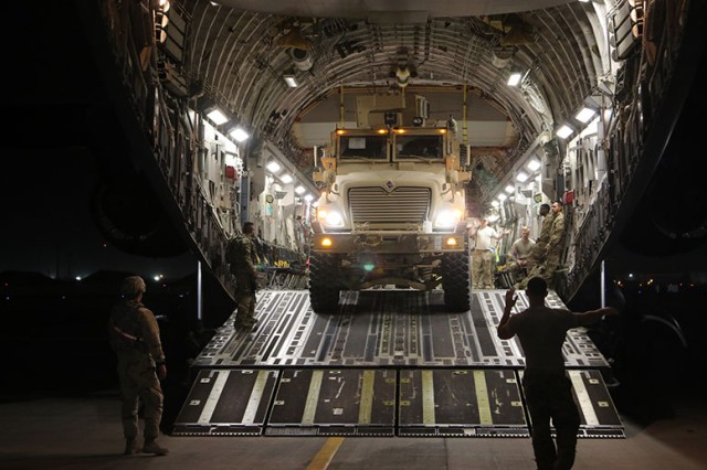 Soldiers assigned to the 1st Armored Division Sustainment Brigade load two Mine-Resistant Ambush Protected vehicles onto an Air Force C-17 aircraft on Bagram Airfield, Afghanistan, June 26, 2017. The brigade helped transport cargo, including fuel and vehicles, across the country during their deployment last year. Some of the cargo will support the Army's first Security Force Assistance Brigade when it deploys this spring.
