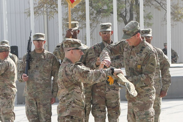 Col. Michael Lalor, left, commander of the 1st Armored Division Sustainment Brigade, and Command Sgt. Maj. Sean Howard, the brigade's senior enlisted adviser, case the brigade's colors at Bagram Airfield, Afghanistan, at the end of their deployment in early November 2017. The brigade helped transport cargo, including fuel and vehicles, across the country. Some of the cargo will support the Army's first Security Force Assistance Brigade when it deploys this spring.