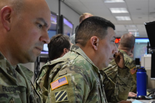 Maj. Ricardo Fregoso (left) and Sgt. 1st Class Jose Arellano monitor their stations while participating in the annual command post exercise Keen Edge 18, held 26 Jan. to 3 Feb. at Joint Base Pearl Harbor Hickam.The exercise allowed service members to hone and refine the steps they would take in the event of a crisis or contingency while executing integrated air and missile defense operations supporting the Pacific theater operation plans.
