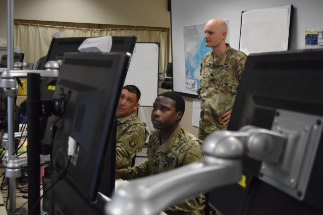 Capt. Adrian Hill (right) and Sgt. 1st Class Jose Arellano (far left) brief Lt. Col. Jonathan Stafford while monitoring their stations. The Soldiers were participating in the annual command post exercise Keen Edge 18, held 26 Jan. to 3 Feb. at Joint Base Pearl Harbor Hickam. The exercise allowed service members to hone and refine the steps they would take in the event of a crisis or contingency while executing integrated air and missile defense operations supporting the Pacific theater operation plans.