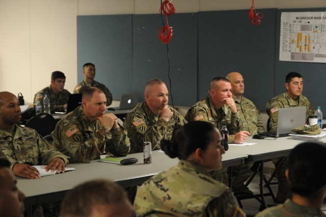 Col. Nick Ducich, center, commander of the Cal Guard 79th Infantry Brigade Combat Team, is briefed by his staff at Camp McGregor, New Mexico, on Jan. 31 during a Mission Rehearsal Exercise (MRX) in preparation for a deployment to Kosovo.