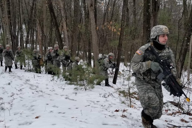 Pvt. Nick Masterlaerz, an infantryman with Charlie Company, 3rd of the 172nd Infantry Regiment (Mountain), NHARNG, leads a squad of Soldiers through the woods of Fort Devens, Mass., Feb. 10. The Soldiers trained with Canadian reserve troops during a multinational training exercise.