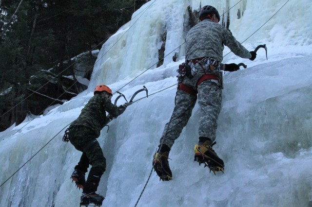 MCpl Alec Ward, left, a Canadian infantryman with the Princess Louise Fusiliers, and Spc. Hunter Cote, an infantryman with Charlie Company, 3rd of the 172nd Infantry Regiment (Mountain), NHARNG, scale the face of Cathedral Ledge, a frozen waterfall in North Conway, N.H., Feb. 12. The training was part of a multinational exercise that focused on infantry tactics, cold weather operations and mountaineering.