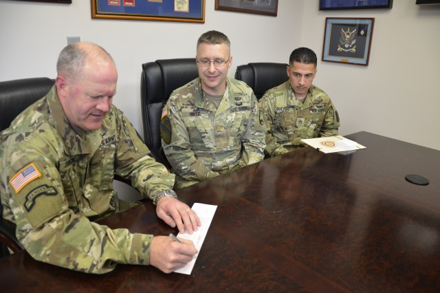 campaign coordinator Maj. Matt Hintz and Staff Sgt. Julian Quevedo watch as Maj. Gen. Pete Johnson, Fort Jackson and Army Training Center commander, signs his Army Emergency Relief donation slip Feb. 9. The Fort Jackson 2018 AER campaign kicks off Feb. 23.