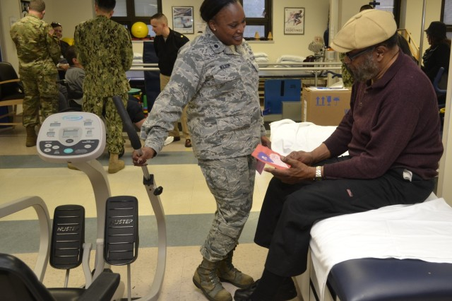 Air Force Lt. Col. Chiriga Wilson presents a thank you card to a patient receiving physical therapy at the Corporal Michael J. Crescenz Veterans Affairs Medical Center, Feb. 12, 2018 in Philadelphia. Volunteers from DLA Troop Support visited the medical center in support of National Salute to Veteran Patients Week.