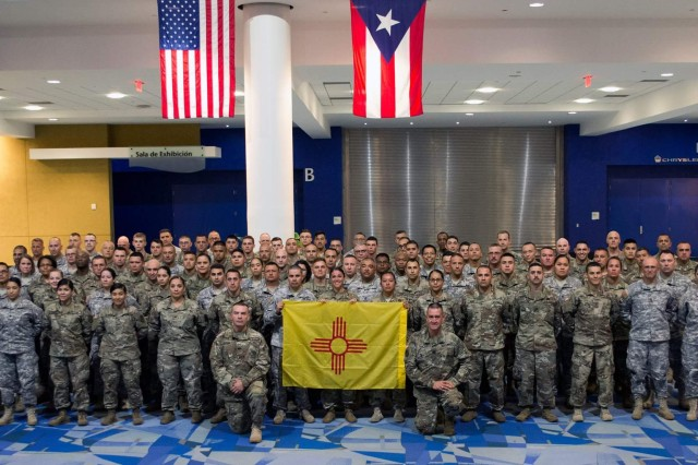 Members of the New Mexico Army National Guard who deployed to Puerto  Rico in support of hurricane relief operations pose with the New Mexico flag.