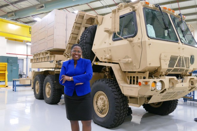 Dr. Juanita Harris poses in front of the Multi-Mission Launcher, a technology designed by the U.S. Army Aviation and  Missile Research, Development and Engineering Center.