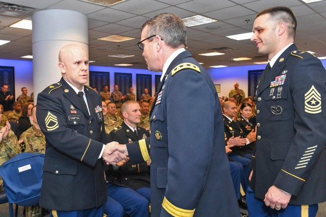 Sgt. 1st Class Joseph Compton, left, shakes hands with Lt. Gen. Thomas Seamands, the Army's G-1, during an award ceremony for the Secretary of the Army Career Counselor of the Year in the Pentagon in Arlington, Va., Feb. 7, 2018. Compton was selected as the reserve component winner in this year's competition.
