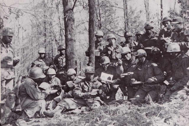 Black Soldiers from 3rd Armored Division take a break from training in the woods at Fort Knox in the early '50s to enjoy a Valentine's Day mail call.