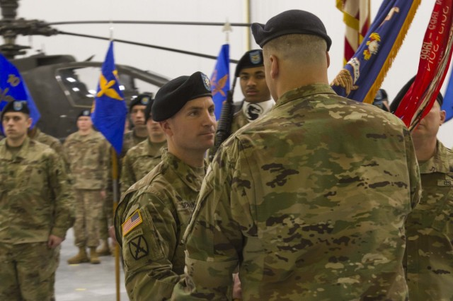 Lt. Col. James Scullion receives the battalion guidon during a change of command ceremony at Fort Drum, New York, on February 8. The passing of the guidon, here by Col. Clair Gill, commander of the 10th Combat Aviation Brigade, represents Scullion taking command of 1-10 Attack Reconnaissance Battalion.  (U.S. Army photo by Spc. Thomas Scaggs) 170208-A-TZ475-093