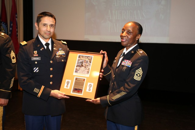 Maj. Jose Moreno, acting commander of 78th Signal Battalion, presents Keynote Speaker Sgt. Maj. Barbara O'Hara, assistant inspector general for U.S. Army Japan, with an appreciation award for her participation in the Black History Month Observance Feb. 15, 2018 at Camp Zama's Community Recreation Center. (U.S. Army photo by Lance D. Davis)