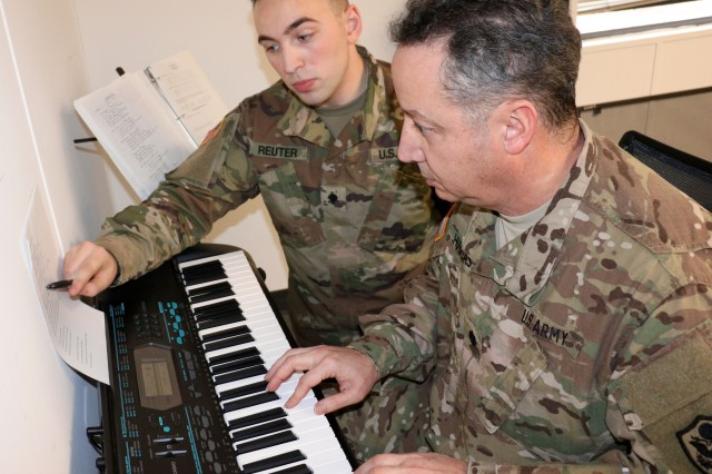 FORT CAMPBELL, Ky.— Spc.. Walter Reuter, a pianist with the 101st Airborne Division Band, helps Lt. Col. Arnaldo Huertas, a Soldier with the Fort Campbell Warrior Transition Battalion, play through a challenging section of a song during a music lesson, Feb. 1. The battalion's Occupational Therapy department partners with the 101st Airborne Division Band to provide musical instruction to Soldiers at the WTB. Playing a musical instrument helps Soldiers improve hand-eye coordination and manual dexterity, improves concentration and helps regulate mood. U.S. Army photo by Maria Yager.