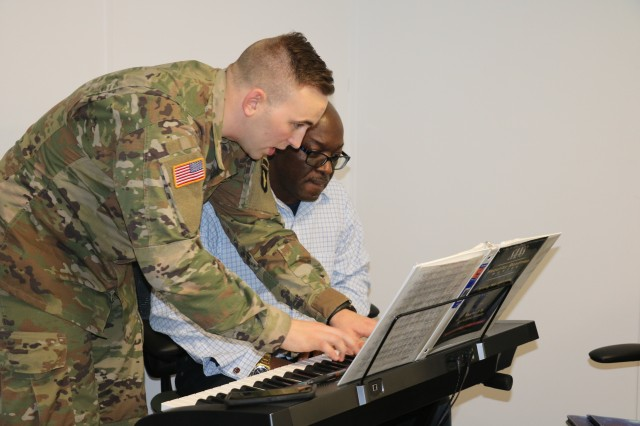 FORT CAMPBELL, Ky. — Spc. Walter Reuter, a pianist with the 101st Airborne Division Band, shows Fort Campbell Warrior Transition Battalion Soldier Chief Warrant Officer 3 Jonathan Dobey how to play a section of music on the keyboard. Dobey played music before injuring his shoulder in the line of duty and participates in a music class sponsored by the WTB's Occupational Therapy department as he recovers. Playing a musical instrument helps Soldiers improve hand-eye coordination and manual dexterity, improves concentration and helps regulate mood. U.S. Army photo by Maria Yager.