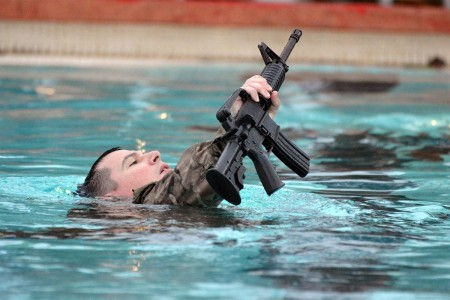 A Soldier assigned to the 25th Infantry Division, performs the 25-meter surface swim with a rubber M4 carbine portion of the Combat Water Survival Test at Schofield Barracks, Hawaii, Jan. 19, 2018. The purpose of CWST is to assess a Soldier's water survival abilities and build confidence.