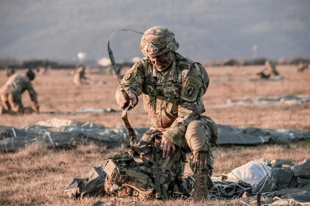 A Soldier is preparing his equipment for combat after landing on Juliet Drop Zone in northern Italy.