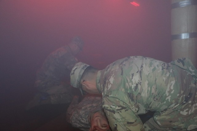 """Capt. Matthew Bern and Sgt. 1st Class Vincent Benitez, both with the 2-360th Training Support Battalion, 120th Infantry Brigade, perform first aid on a life-like mannequin in the """"smoke room"""" during Combat Lifesaver training at Camp Parks, Calif., Feb. 15, 2018. To add realism to the training, the smoke room has a purple haze and sound system that simulates small arms fire and grenades."""