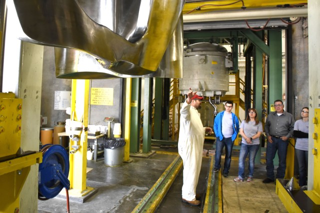 Brian Byrd (left) talks to visitors from Leadership McAlester about industrial-size mixer that is used to prepare explosive fills for bombs during a Feb. 15 tour of McAlester Army Ammunition Plant, Okla.