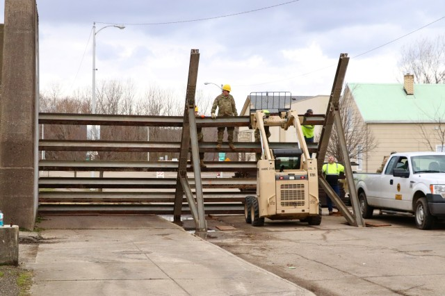 Soldiers of the 1191st Engineer Company and members of the city of Portsmouth Flood Defense Division use a skid steer loader to maneuver a steel beam into place as they erect floodgates in Portsmouth, Ohio, Feb. 19, 2018. The 1191st erected two floodgates at breaks nearest the Ohio River, which are a precautionary measure in response to flood waters on the river that are more than five feet above flood stage.