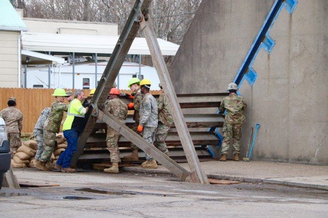 Soldiers of the 1191st Engineer Company and members of the city of Portsmouth Flood Defense Division emplace steel beams that provide the framework for floodgates in Portsmouth, Ohio, Feb. 19, 2018. The 1191st erected two floodgates at breaks nearest the Ohio River, which are a precautionary measure in response to flood waters on the river that are more than five feet above flood stage.