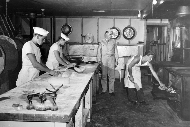 A former German prisoner of war during World War II, Heino Erichsen served out his military time at Fort Knox in 1945 and eventually settled in Texas. In this photo, Erichsen pulls rolls from an oven while Maj. John Warrick supervises him and other German POWs. Later, Erichsen wrote a moving autobiography of his time at the Army post, titled The Reluctant Warrior. He also visited the post on a number of occasions throughout the years. Two of his sons graduated from basic training and later served at the post. Erichsen last visited in 2009, and his speech was published in the Fort Knox Turret. Erichsen died Jan. 13, at the age of 93.