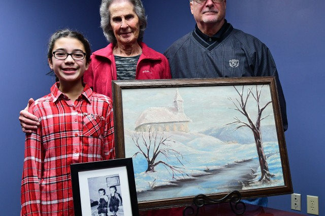 (From right) Eric Brandenburg, his mother Martha (Atcher) Brandenburg, and niece Skyler Brandenburg, 10, stand behind a painting that has been in the family since the 1940s, when a German prisoner of war painted it and presented it to Martha's father as a gift.