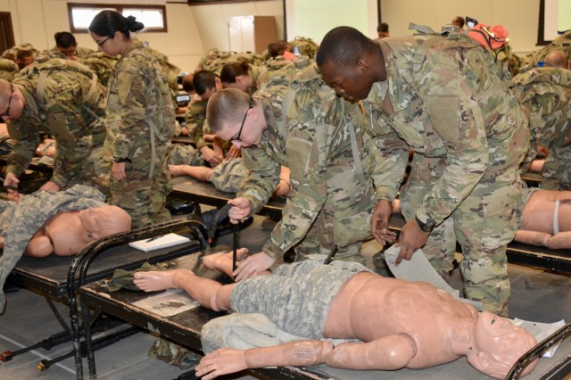 From left, Spc. Eric Nagy and Pfc. Jared Nelson, Company F, 1st Battalion, 48th Infantry Regiment, take turns applying a tourniquet to a dummy during first aid training.
