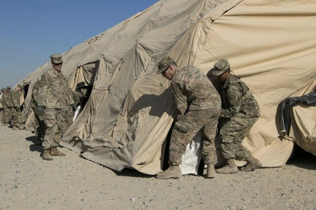 35th Infantry Division Soldiers work together during the Blaze the Trail exercise at Camp Arifjan, Kuwait Jan. 11, 2018. Soldiers set up a deployable rapid assembly shelter for division staff to operate from during the training exercise.