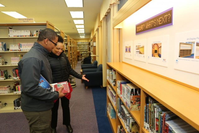James Elliot, left, a junior at ZAMHS, Rashunda Clement, right, Children and Youth Services coordinator, look at some of the books available Feb. 22, 2018 during the Camp Zama Library Teen Station's grand opening. (U.S. Army photo by Lance D. Davis)
