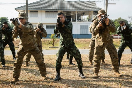Royal Thai Army soldiers and U.S. Army Soldiers from the 25th Infantry Division, aim their weapons during military operations on urban terrain training event during Exercise Cobra Gold on Camp Friendship in Korat, Kingdom of Thailand, Feb. 13, 2018. The U.S. Army is wearing an experimental jungle combat uniform for the duration of the exercise.