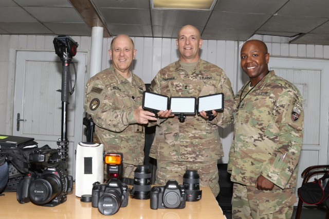 Navy Cmdr. Jim Wiltraut, Combined Security Transition Command-Afghanistan's Public Affairs director; Army Maj. Gen. L. Neil Thurgood, CSTC-A's deputy commanding general; and Army Sgt. 1st Class E. L. Craig, CSTC-A's Public Affairs senior noncommissioned officer, show off their newly received Tactical Digital Media equipment in July 2017.