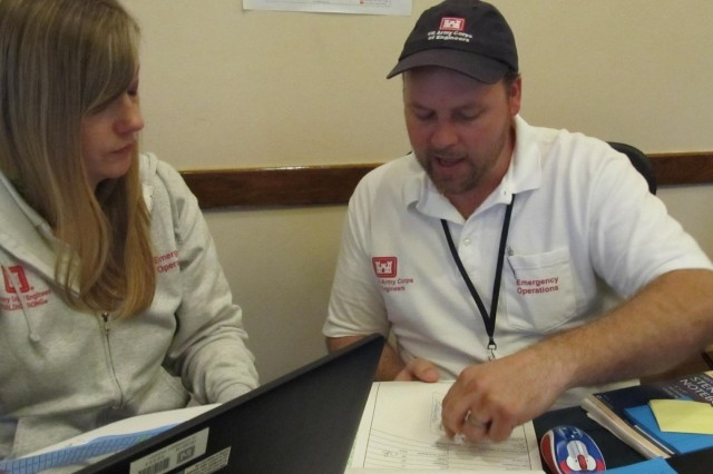 U.S. Army Corps of Engineers Deputy Resident Engineer Benjamin Bremer discusses duplicate Right of Entry applications and Temporary Roof (Blue Roof) discrepancies with Data and Invoice Manager Heather Pobst, Dorado Puerto Rico, February 22, 2018.