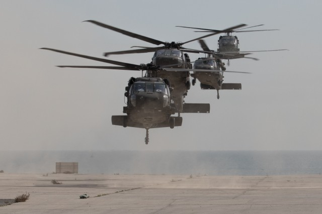 UH-60 Black Hawk helicopters carrying distinguished visitors arrive for Army Day 2018, Feb. 9, 2018, Kuwait Naval Base, Kuwait. Army Day was the opening event for U.S. Central Command's Component Commanders Conference, which allowed U.S. Army Central to showcase the Army's capabilities at the theater level.