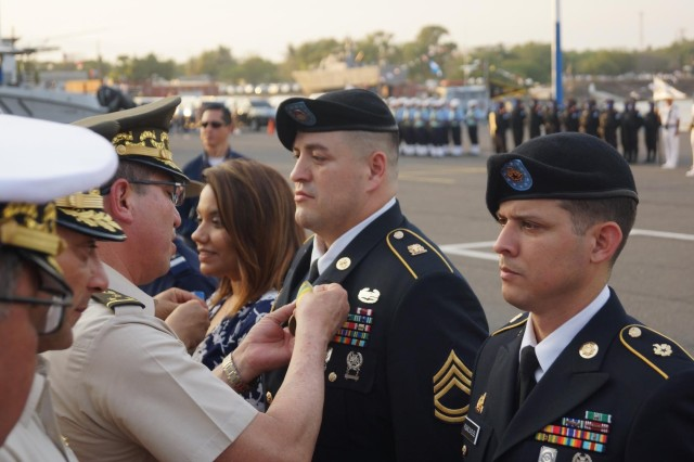 Guatemalan general officer pins the Medalla Monja Blanca on Sgt. 1st Class Michael Kinzie and Staff Sgt. Harcel Rosado, right. Not shown is award recipient Chief Warrant Officer 4 Raul Espinoza. They were recognized for acts of brotherhood to the Central American nation.
