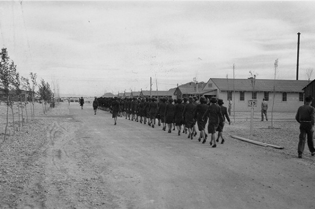WAACs at Dugway Proving Ground, Utah, march to their first meal shortly after arriving on April 20, 1943. Note the many young trees planted by the roadway, purchased at the expense of Dugway's first commander Col. John Burns. After the war, when Dugway was closed, the trees were removed for replanting to Deseret Depot. Unknown photographer