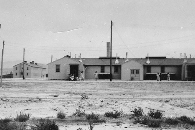 Rear of Women's Army Corps (WAC) barracks at right, as it appeared 1943 to 1946, in Dog (later, Ditto) Area at Dugway Proving Ground, Utah. Dugway was among the first, few installations in the nation to receive a WAAC unit when the program was new in 1943. To free male Soldiers for the war, trained women took over their roles as mechanics, cooks, lab assistants, photographers, drivers, mortar gunners for tests and the like. The two-story building to the right of the water tower is the officers' quarters. Unknown photographer.