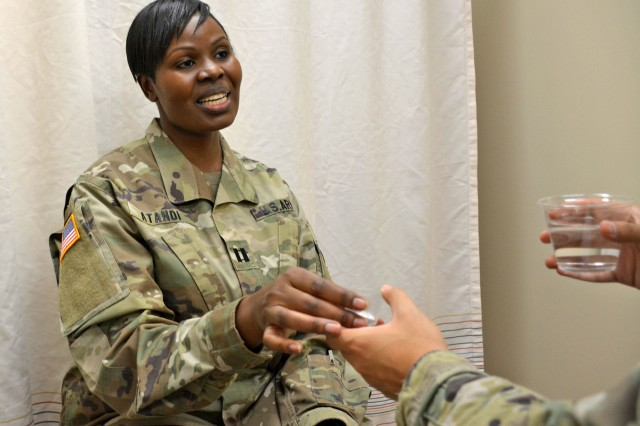 Capt. Everline Atandi, Army Public Health Nurse at Tripler Army Medical Center dispenses medication to patient for Latent Tuberculosis Infection Direct Observation Therapy treatment at Tripler Army Medical Center, Feb. 6, 2018.