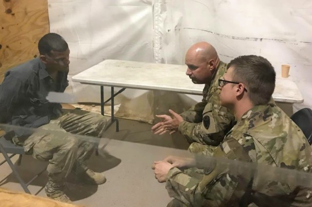 """Staff. Sgt. Jason Calhoun (back right) and Spc. Aaron Szychowski (front right) conduct a mock interrogation with a detainee role-player during the """"Griffin Watch"""" exercise at McGregor Base Camp, New Mexico."""