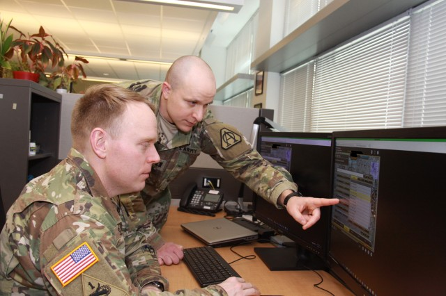 Capt. Doug Williams (standing) and Capt. Jake Singleton review the Joint Battle Command-Platform's new interactive multimedia instruction software at Aberdeen Proving Ground, Maryland, on Jan. 10, 2018. The IMI software will allow Soldiers to train on JBC-P from a CD, the Army's online training tool LandWarNet, or embedded on vehicle hardware known as Mounted Family of Computing Systems.
